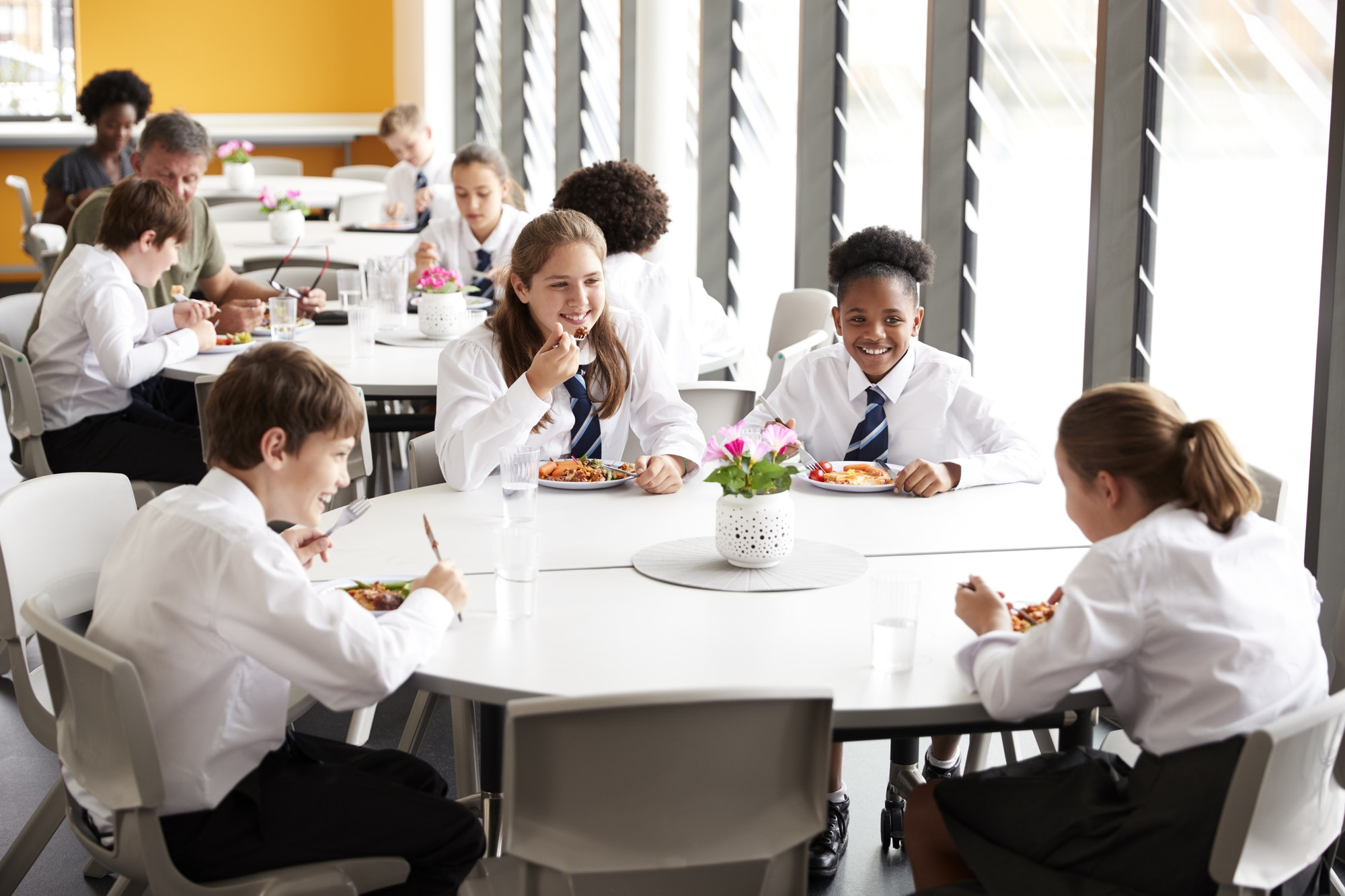 Group Of High School Students Wearing Uniform Sitting Around Table And Eating Lunch In Cafeteria